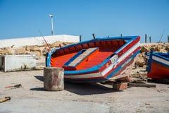 在岸的红色小船 维修服务 免版税库存照片