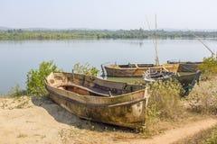 在岸的老残破和被放弃的小船反对河和绿色森林的背景 免版税图库摄影