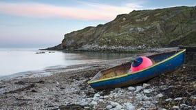 在岸的蓝色小船在Lulworth小海湾 图库摄影