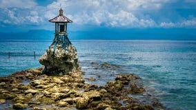 在岸的逗人喜爱的寺庙由努沙的Penida海有在巴厘岛,印度尼西亚上的剧烈的云彩的 免版税库存照片