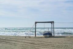 在岸附近的大波浪与一条白色和蓝色小船 图库摄影