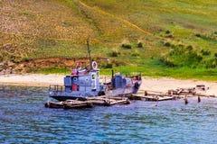 在岸附近的老铁小船 库存照片