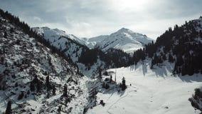 在峡谷的距离峰顶的多雪的山峰的全景用雪包括 沿那里峡谷的边 股票视频