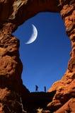 在峡谷远足者的岩层Silhouetter的曲拱 库存图片