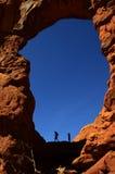 在峡谷远足者的岩层Silhouetter的曲拱 免版税图库摄影