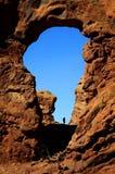 在峡谷远足者的岩层Silhouetter的曲拱 免版税库存图片