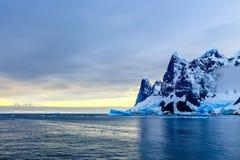 在峭壁、蓝色冰川和漂移的冰山的日落用水 库存图片