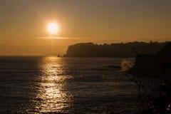 在峭壁和海的日落 库存图片