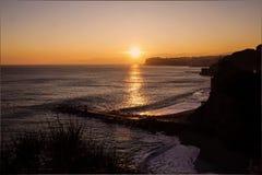 在峭壁和海的日落 免版税库存照片