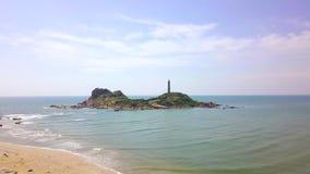 在峭壁海岛上的灯塔蓝色海寄生虫视图的 在岩质岛上的鸟瞰图灯塔海洋和天空蔚蓝的 影视素材