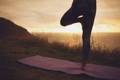 在峭壁的女子实践的瑜伽在日落 库存图片