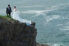 在峭壁的婚礼夫妇 库存图片