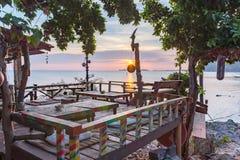 在峭壁的嬉皮酒吧在日落的海 库存照片