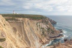 在峭壁的灯塔在海洋附近 免版税库存图片