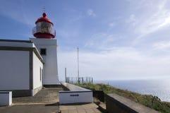 在峭壁的白色浪漫灯塔,西部马德拉岛海岛,村庄Ponta做Pargo,葡萄牙,大西洋 免版税库存照片