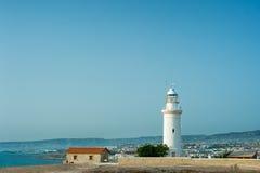在峭壁的白色灯塔 开花前景桃红色海边城镇 免版税库存图片