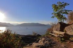 在峭壁的长凳在晚上太阳的光芒与 免版税库存图片