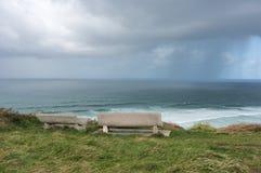 在峭壁的长凳在有风雨如磐的云彩的海附近 免版税库存照片