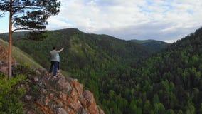 在峭壁边缘的一个年轻夫妇立场和享受美丽的景色 影视素材
