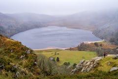 在峭壁边缘的人身分在展望遥远的薄雾覆盖物湖和山未来的水库的考虑clea 免版税图库摄影