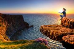 在峭壁边缘的凝思在日落 库存照片