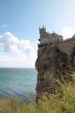 在峭壁边缘的老城堡燕子的巢在蓝色海上 免版税库存图片