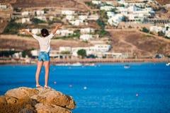 在峭壁边缘的年轻愉快的女孩有老小村庄惊人的看法在米科诺斯岛,希腊语 库存照片