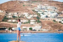 在峭壁边缘的年轻愉快的妇女有老小村庄惊人的看法在米科诺斯岛,希腊语 免版税库存照片