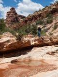 在峭壁顶部的人在沙漠 库存照片