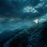 在峭壁顶部的孤独的少妇在晚上 库存照片