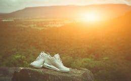 在峭壁` s边缘的一个大岩石上把放的旅行鞋子 库存照片