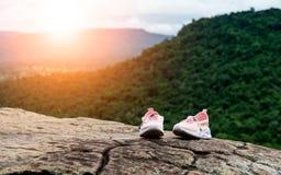 在峭壁` s边缘的一个大岩石上把放的旅行鞋子 免版税库存照片