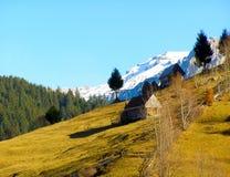 在峰顶房子的白色山雪 库存图片