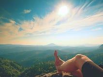 在峰顶的赤裸男性腿做步 在谷上的砂岩岩石与没有鞋子的疲乏的远足者腿 免版税库存照片