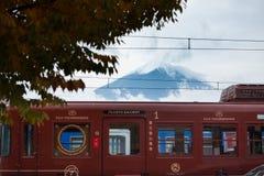 在川口驻地的Fujikyu火车红色汽车与富士山在背景中 免版税图库摄影