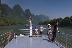 在巡航在李河和看高石灰石山的小船的中国家庭在阳朔附近在中国 免版税库存照片