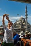在巡航小船的女性旅游采取的selfie照片在伊斯坦布尔 免版税库存照片