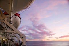 在巡航轮渡船的一艘白色救生艇在天空下 库存图片