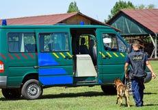 在巡逻车旁边维持有他的狗的人治安 免版税图库摄影