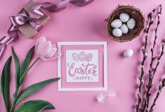 在巢和郁金香花的复活节彩蛋在与复活节卡片的桃红色背景 等待的春天 库存照片