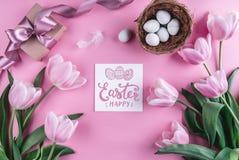 在巢和郁金香花的复活节彩蛋在与复活节卡片的桃红色背景 库存照片