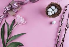 在巢和郁金香花的复活节彩蛋在春天背景 与拷贝空间的顶视图 看板卡愉快的复活节 免版税库存图片