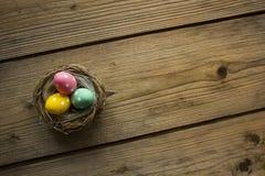 在巢的五颜六色的复活节彩蛋在木桌上 图库摄影