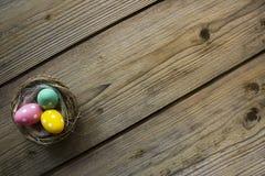 在巢的五颜六色的复活节彩蛋在木桌上 免版税库存图片