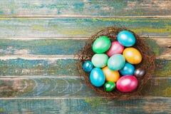 在巢的五颜六色的复活节彩蛋在木土气背景顶视图 3d美国看板卡上色展开标志问候节假日信函国民形状范围 图库摄影
