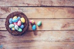 在巢的五颜六色的复活节彩蛋在与空间的木背景 图库摄影