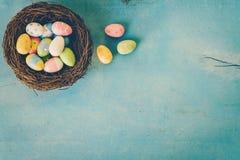在巢的五颜六色的复活节彩蛋在蓝色淡色木头backgr 免版税图库摄影
