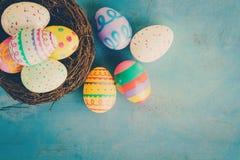 在巢的五颜六色的复活节彩蛋在蓝色淡色木头backgr 库存照片