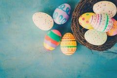 在巢的五颜六色的复活节彩蛋在蓝色淡色木头backgr 免版税库存照片