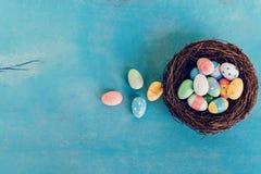 在巢的五颜六色的复活节彩蛋在蓝色淡色木头backgr 免版税库存图片